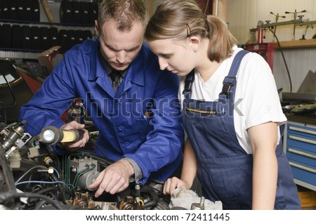 Auto mechanic shows the female trainee maintenance of the car in workshop in front of a car - stock photo