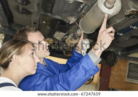 Auto mechanic shows the female trainee maintenance of the Car muffler under a car on a hoist - stock photo