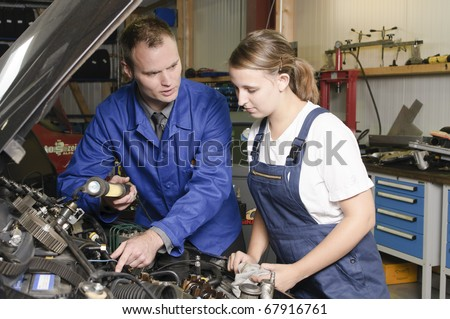 Auto mechanic shows the female trainee maintenance of the engine in workshop in front of a car on open hood - stock photo