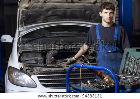 Auto mechanic standing near car at repair shop - stock photo