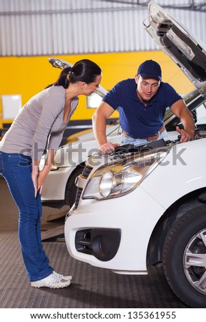 auto mechanic talking to female customer in front of her car with bonnet open - stock photo