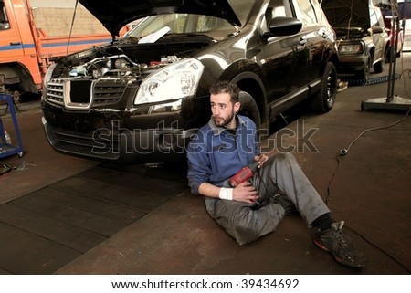 auto mechanic with car in his workshop - stock photo