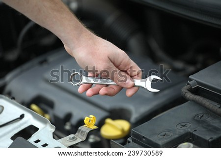 Auto mechanic with iron spanners in closeup. Auto mechanic in car repair  - stock photo