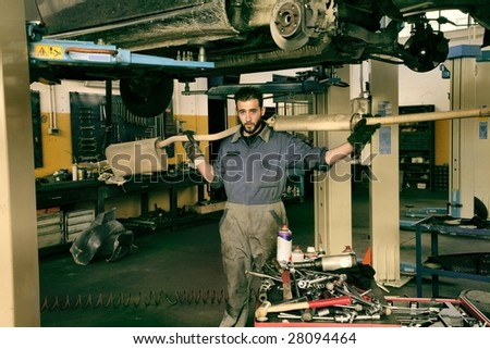 auto mechanic with silencer - stock photo