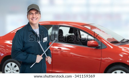 Auto mechanic with tire wrench in garage. Car repair service. - stock photo