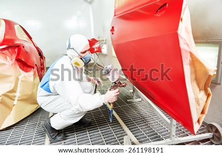 auto mechanic worker painting a red car in a paint chamber during repair work - stock photo