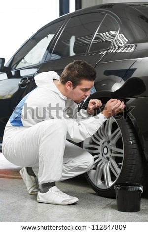 auto mechanic worker painting element car at automobile repair and renew service station shop by power buffer machine - stock photo