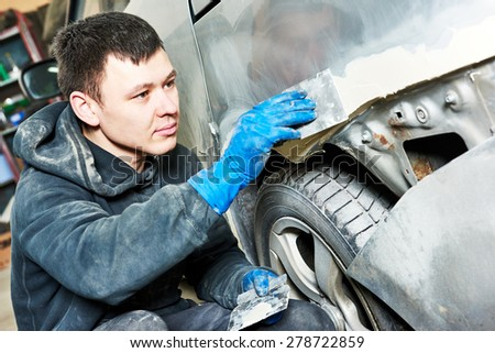 auto mechanic worker plastering body car at automobile repair and renew service station shop before painting restoration - stock photo