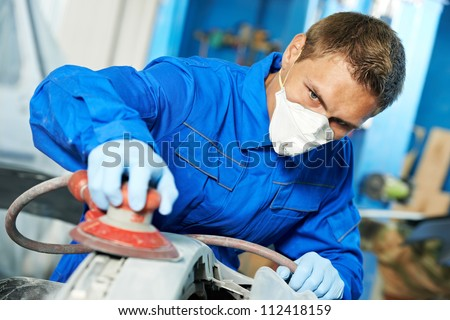 auto mechanic worker polishing bumper car at automobile repair and renew service station shop by power buffer machine - stock photo