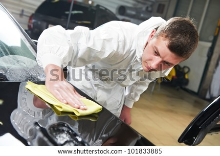 auto mechanic worker polishing car bonnet with wiper at automobile repair and renew service station shop - stock photo