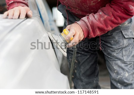 auto mechanic worker polishing the basic layer of car body - stock photo