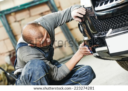auto mechanic worker sanding polishing bumper car at automobile repair and renew service station shop by sandpaper - stock photo