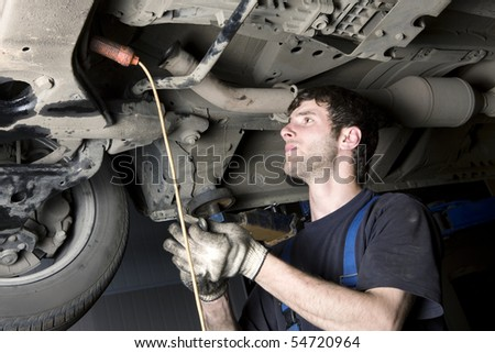 Auto mechanic working at auto repair shop - stock photo