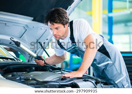 Auto mechanic working in car service workshop - stock photo