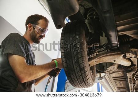 Auto Mechanic Working In Garage. Repair Service - stock photo