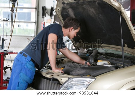 Auto mechanic working on a car in garage - stock photo