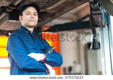 Auto mechanic working on a car in his garage - stock photo