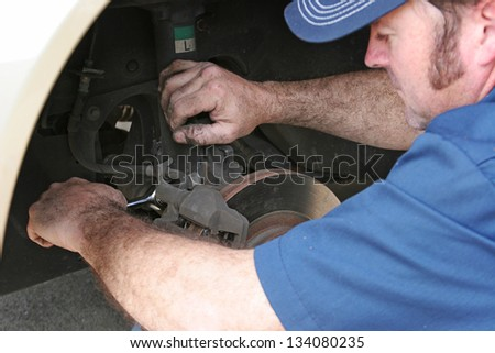 Auto mechanic working on a car's front disc brakes. - stock photo