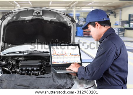Auto mechanic working on a computer connected to a car engine at repair shop - stock photo