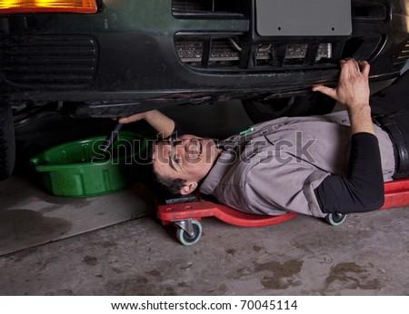 Auto mechanic working under a car - stock photo