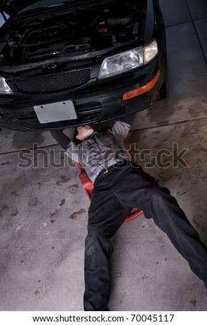 Auto mechanic working under a car repairing an engine - stock photo