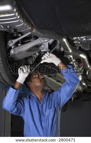 Auto mechanic working under car - stock photo