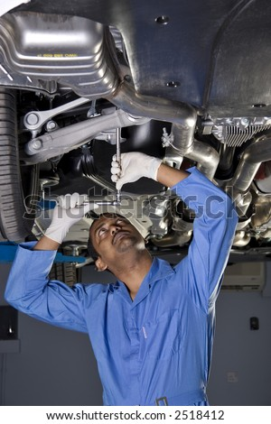 auto mechanic working under car on a lift - stock photo