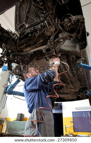Auto mechanic working under the car - stock photo