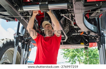Auto mechanic working underneath a lifted  - stock photo