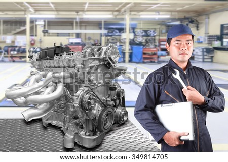 Auto mechanics holding a computer and tool for repair engine car at repair shop service - stock photo