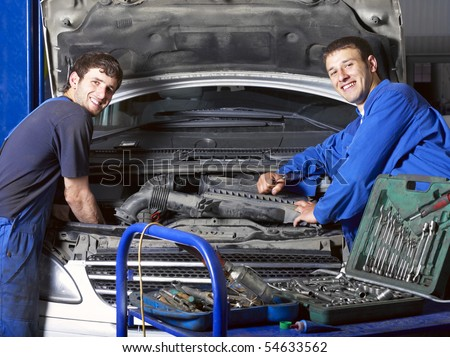 Auto mechanics near car. Different working tools on foreground - stock photo