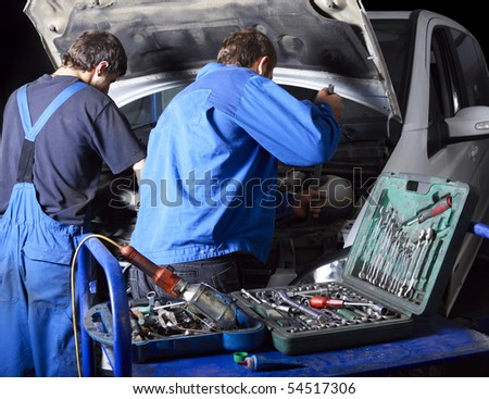 auto mechanics repairing a car engine. Different working tools on foreground - stock photo