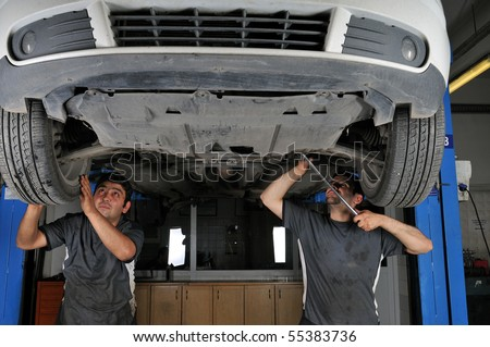 Auto mechanics working under the car - a series of MECHANIC related images. - stock photo