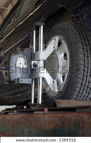 Auto on precision wheel alignment jig. Laser used for pin point accuracy in making sure wheels track properly. - stock photo