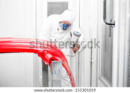 Auto painter spraying red paint on car front bumper in special booth