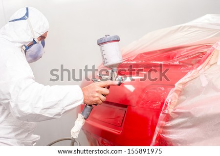 Auto painter spraying red paint on car in auto workshop - stock photo