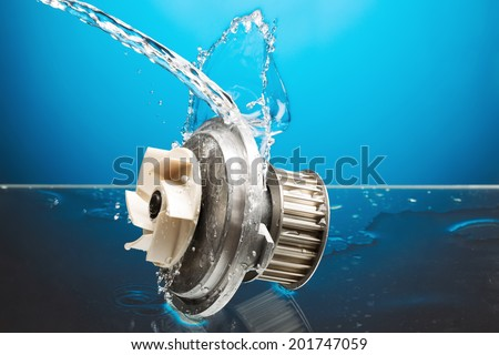 Auto parts, engine cooling pump in water splash on blue gradient background - stock photo