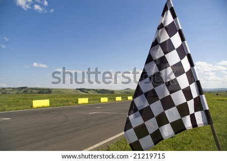 Auto racing checkered flag on a background of the  blue sky.