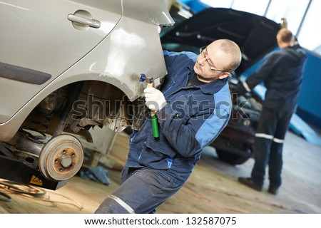 auto repair man worker flatten and align metal body car with hammer in automotive industry - stock photo