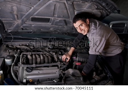 Auto Repair Mechanic under the hood - stock photo