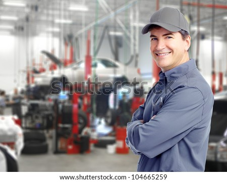 Auto repair service. Handsome smiling mechanic. - stock photo