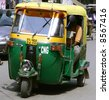 auto rickshaw driving on road, delhi, india - stock photo