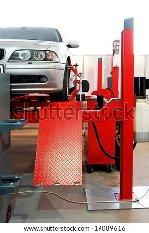 Auto service garage with car at lift - stock photo