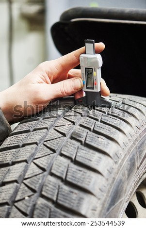 auto service man worker measuring rubber car wheel tyre protector - stock photo