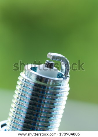 Auto service. New car spark plug as spare part of auto transportation on blurry green background. - stock photo