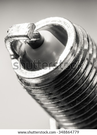 Auto service. New car spark plug as spare part of auto transportation on gray background. - stock photo