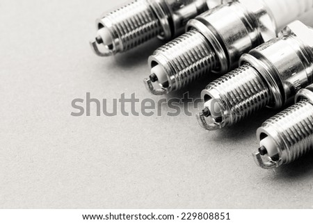 Auto service. Set of new car spark plugs as spare part of auto transportation on gray - stock photo