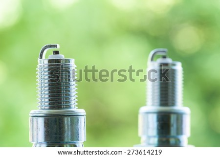 Auto service. Two new car spark plugs as spare part of auto transportation on blurry green background. - stock photo