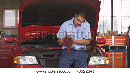 Auto shop mechanic talking on cell phone - stock photo