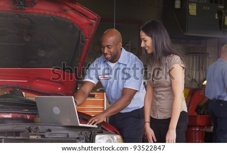 Auto shop mechanic working on laptop computer with customer